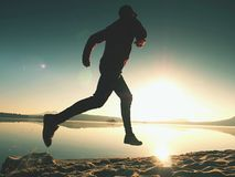 Silhouette of active athlete runner running on sunrise shore. Morning healthy lifestyle exercise. On sandy beach. Man long jumping at ocean, sprinting with high stock image