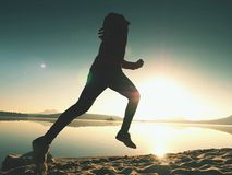 Silhouette of active athlete runner running on sunrise shore. Morning healthy lifestyle exercise. On sandy beach. Man long jumping at ocean, sprinting with high stock photos