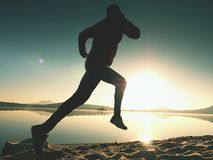 Silhouette of active athlete runner running on sunrise shore. Morning healthy lifestyle exercise. On sandy beach. Man long jumping at ocean, sprinting with high royalty free stock images