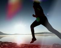 Silhouette of active athlete runner running on sunrise shore. Morning healthy lifestyle exercise. On sandy beach. Man long jumping at ocean, sprinting with high stock photography
