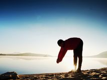 Silhouette of active man exercising  and stretching on the lake beach at sunrise. Stock Photo