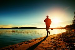 Silhouette of active man running and exercising on the beach at sunset. Royalty Free Stock Photos
