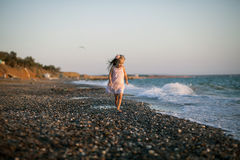 Silhouette of adorable little girl on a beach at. Sunset. This image has attached release Stock Image
