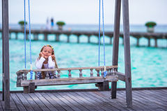 Silhouette of adorable little girl on a swing at Royalty Free Stock Photos