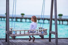 Silhouette of adorable little girl on swing at Stock Photo