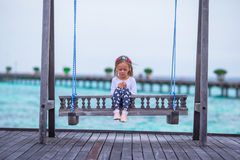 Silhouette of adorable little girl on swing at Stock Photography