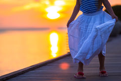 Silhouette of adorable little girl on wooden jetty Stock Image
