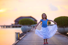 Silhouette of adorable little girl on wooden jetty Stock Photo