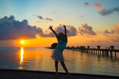 Silhouette of adorable little girl on wooden jetty Royalty Free Stock Images