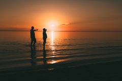 Silhouette of adult couple standing in the sea against a sunset. Evening photo Royalty Free Stock Image
