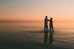 Silhouette of adult couple standing in the sea against a sunset. Stock Photos