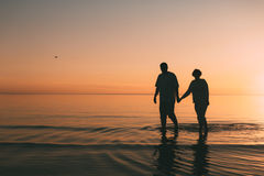 Silhouette of adult couple standing in the sea against a sunset. Evening photo Stock Image