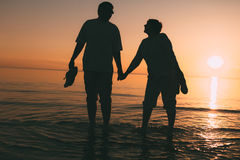 Silhouette of adult couple standing in the sea against a sunset. Royalty Free Stock Image
