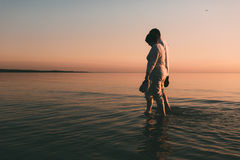 Silhouette of adult couple standing in the sea against a sunset. Evening photo Royalty Free Stock Photo