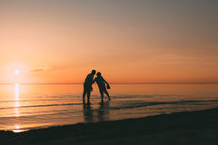 Silhouette of adult couple standing in water want to kiss. Stock Photos