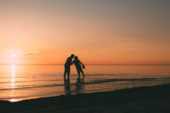 Silhouette of adult couple standing in water want to kiss. Royalty Free Stock Images