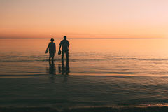 Silhouette of adult couple which costs in the sea and holds in hand footwear. Stock Photography