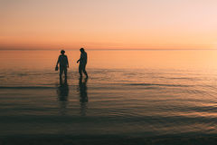 Silhouette of adult couple which costs in the sea and holds in hand footwear. Royalty Free Stock Image