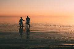 Silhouette of adult couple which costs in the sea and holds in hand footwear. Stock Image
