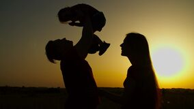 Cheerful family with baby girl relaxing at sunset