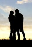 Silhouette affectueuse de couples tenant des mains au coucher du soleil Image libre de droits