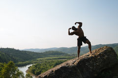 Silhouette of african american bodybuilder with naked torso posing on the rock. Green mountain nature background Stock Photo