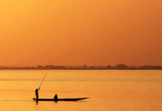 Silhouette of African fisherman in canoe Stock Photography