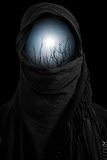 Silhouette against sun in black veil with dark environment Stock Photography