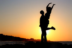 Silhouette of ahappy couple by the sea silhouette Stock Photos