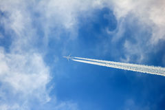 Silhouette of aircraft flying in the clouds and leaving contrail Royalty Free Stock Images