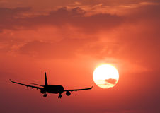 Silhouette of a airplane and colorful sky with sun Stock Images