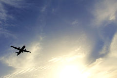 A silhouette of an airplane flying in the blue sky with white clouds Stock Photography