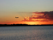 Silhouette of airplane flying in a sunset sky. Over the lake Royalty Free Stock Image