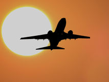 Sunset Flight. A silhouette of an airplane over a huge setting sun Stock Photos