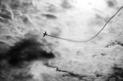 Silhouette of an airplane with smoke; Royalty Free Stock Images