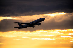 Silhouette of airplane at sunset Stock Images