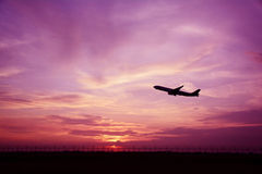 Silhouette of airplane on sunset background. Royalty Free Stock Image