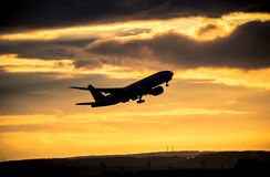 Silhouette of airplane at sunset. Stock Photo