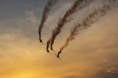 Silhouette of airplane on sunset with smoke in background Stock Photos
