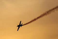Silhouette of airplane on sunset with smoke in background Royalty Free Stock Image