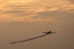 Silhouette of airplane on sunset with smoke in background Stock Image