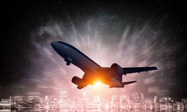 Airliner in sky. Mixed media. Silhouette of airplane taking off and flying away in to sky. Mixed media Stock Image