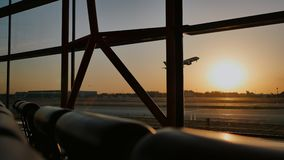 Silhouette of an airplane taking off at sunset at Beijing airport in the background of a window.