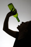 Silhouette of an alcoholic woman with a bottle Royalty Free Stock Photography