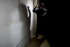 Silhouette of an Alley Stalking Criminal. Hooded criminal stalking in the shadows of a dark street alley Stock Photo