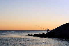 Silhouette of alone fisherman. Fisherman silhouette on sunset with large blank copy space Royalty Free Stock Photos