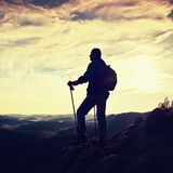 Silhouette of alone hiker with poles in hand. Tourist with sporty backpack stand on rocky view point above misty valley. Sunny spr Stock Photography