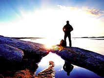 Silhouette of alone man looking toward vibrant sunset. Flare and  reflected in shallow waters Stock Photography