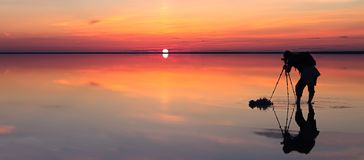 Silhouette of alone man takes a picture of a vibrant sunset reflected in shallow waters of solt lake. Banner size. The photographer takes a picture of the Royalty Free Stock Image