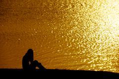 Silhouette alone woman sitting on the grass field near water at. The sky sunset Royalty Free Stock Photos